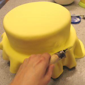 Приминаем мастику к поверхности десерта, излишки обрезаются