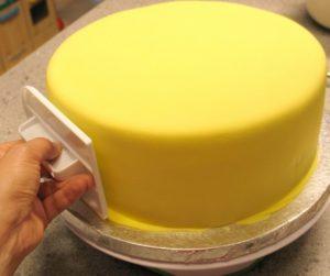 Придавим мастику к торту с помощью любого плоского предмета