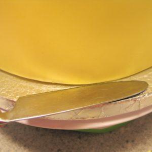 Обрезанные края мастики подминаем под торт