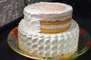 Двухъярусный торт в процессе украшения кремом