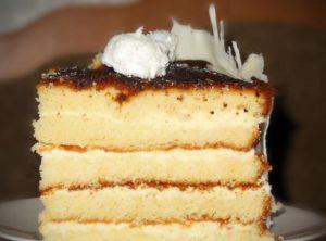 Кусочек готового золотистого торта на основе масляного бисквита с белым шоколадом