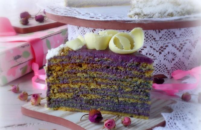 Кусочек готового медового торта с черничным кремом